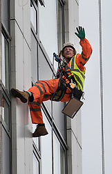 © Licensed to London News Pictures. 27/06/2017. London, UK. A specialist waves as he abseils on the face of Bray tower block to inspect cladding on the Chalcots Estate in Camden after it failed a fire inspection because of combustable cladding. More than 700 flats in tower blocks on an estate in the Swiss Cottage area of north-west London are being evacuated because of fire safety concerns after the Grenfell Tower fire of on June 14. Photo credit: Peter Macdiarmid/LNP