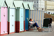 © Licensed to London News Pictures. 18/04/2014. Brighton, UK. A woman reads a paper outside a beach hut. People enjoy the  bank holiday sunshine at Brighton today 18th April 2014. Photo credit : Stephen Simpson/LNP