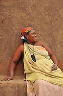 A rural Venda woman potter relaxes against the wall of a traditional building at the Mashamba Pottery. Limpopo, South Africa