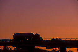 Large liquid transport truck travelling down an elevated stretch of freeway at sunset