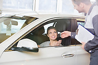 Smiling female customer receiving car key from mechanic in workshop