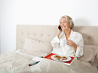 Happy senior woman answering cell phone while having breakfast in bed