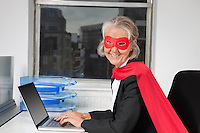 Portrait of senior businesswoman in superhero costume using laptop at office desk