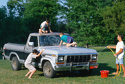 Three boys and a man washing an old pick up truck out in the country