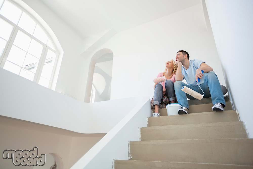 Low angle view of couple with painting tools sitting on steps in new house