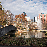 Marshall Park bridge, pond, fountain, Duke Energy Center, and One Wells Fargo Center buildings in Charlotte, North Carolina in the United States of America.