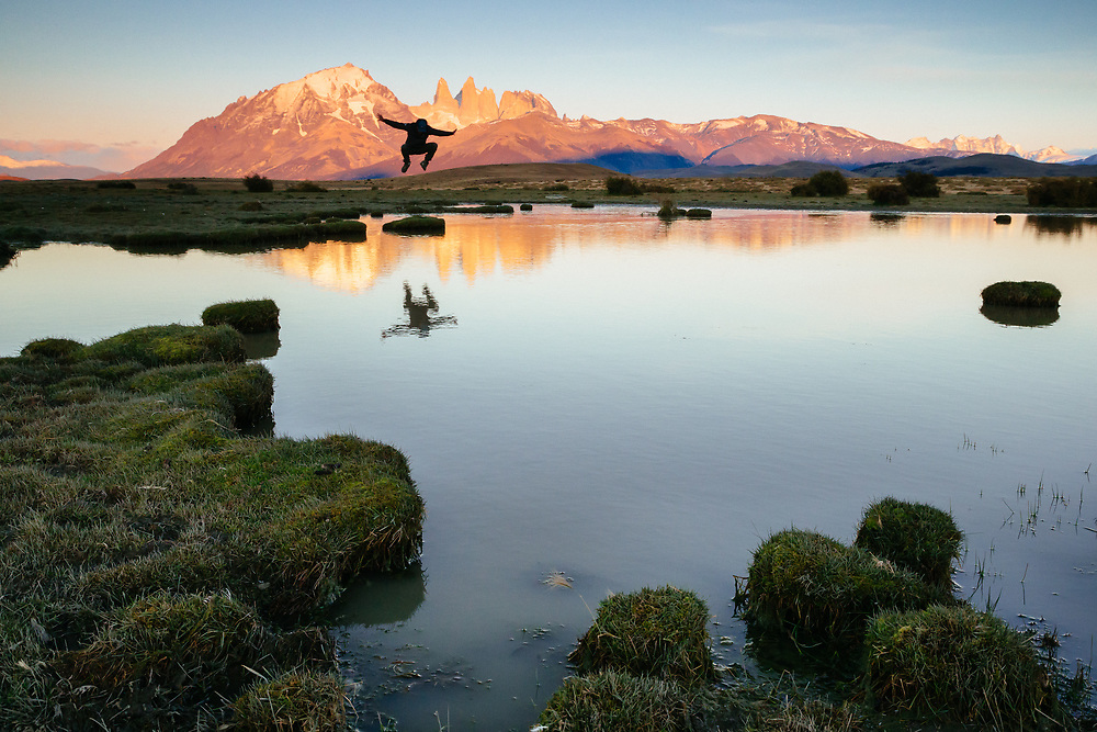 Chris Theobald gets a little air in front of the towers at sunrise in Torres del Paine National Park.