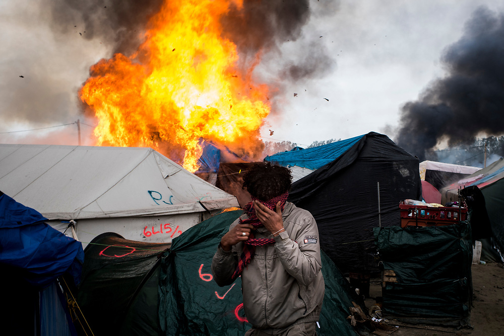 A refugee covers his face in a scarf as fires erupt in The Jungle refugee camp on Wednesday, October 26, 2016 in Calais, France. Fires began breaking out the previous night and continued with escalating frequency, forcing people to flee and destroying large swaths of the camp.