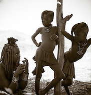 Two Himba girls lean on post in the shade, with a woman starts a sewing project, Northen Namibia, Africa
