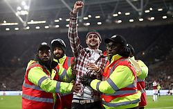 Members of security remove a pitch invader during the Carabao Cup, Fourth Round match at the London Stadium.