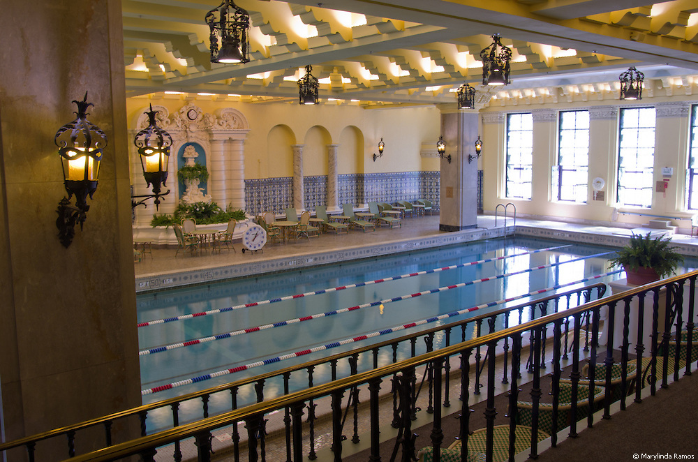 The ornate pool at the Intercontinental Hotel on Chicago's Magnificent Mile is accented with luxurious architectural details such as sconces, decorative textured green glass windows, and stadium seating with green and beige rattan furnishings.