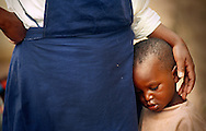 An exhausted child is comforted by a Sister of Mother Teresa at St. Joseph's Center in Kibungo, Rwanda. The child became separated from his parents during their recent journey home from Tanzania.