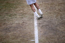 General view of the wear and tear to the grass on the baseline of court eighteen on day eight of the Wimbledon Championships at The All England Lawn Tennis and Croquet Club, Wimbledon.