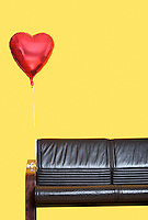 Heart shaped balloon tied to sofa over yellow background