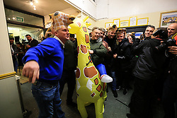 20 February 2017 - The FA Cup - (5th Round) - Sutton United v Arsenal - A Sutton fans rides an inflatable Giraffe flanked by fellow fans wearing Giraffe hats - Photo: Marc Atkins / Offside.