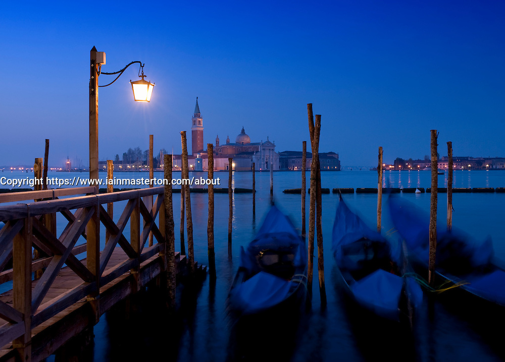 Gondola moorings at night before dawn beside Grand Canal at San Marco in Venice Italy