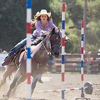 Horse and cowgirl race through a pattern of markers during the pole bending event at the 63rd Annual Woodside Junior Rodeo in Woodside, CA, July 4, 2013.