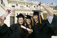 Graduates hoisting diplomas outside university portrait