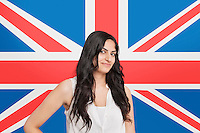 Portrait of beautiful Asian woman smiling against British flag