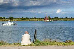 An elderly man watching boats on the Blackwater River in Essex.