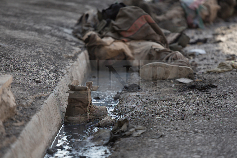 Licensed to London News Pictures. 11/11/2016. Mosul, Iraq. A boot sits in a gutter and beyond the dead bodies of ISIS extremists, killed four days before by Iraqi forces, are seen in Mosul's Al Intisar district on the south east of the city. The Al Intisar district was taken four days ago by Iraqi Security Forces (ISF) and, despite its proximity to ongoing fighting between ISF and ISIS militants, many residents still live in the settlement without regular power and water and with dwindling food supplies.<br /> <br /> The battle to retake Mosul, which fell June 2014, started on the 16th of October 2016 with Iraqi Security Forces eventually reaching the city on the 1st of November. Since then elements of the Iraq Army and Police have succeeded in pushing into the city and retaking several neighbourhoods allowing civilians living there to be evacuated - though many more remain trapped within Mosul.  Photo credit: Matt Cetti-Roberts/LNP