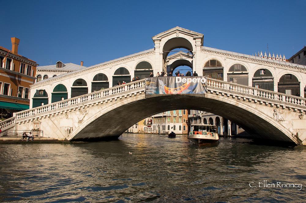 A vaporetto under the Rialto Bridge and The Grand Canal, Venice, Italy