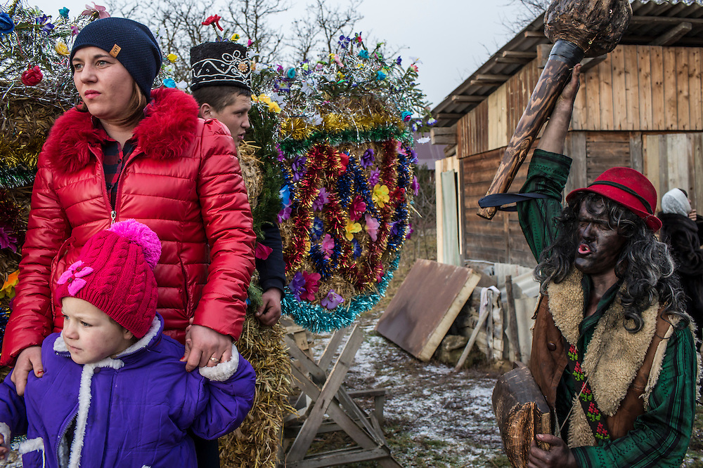 A woman watches with her daughter as revelers in costume celebrate the Malanka Festival on Thursday, January 14, 2016 in Krasnoilsk, Ukraine. The annual celebrations, which consist of costumed villagers going in a group from house to house singing, playing music, and performing skits, began the previous sundown, went all night, and will last until evening.