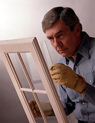workman glazer checks glass for window, safety gloves