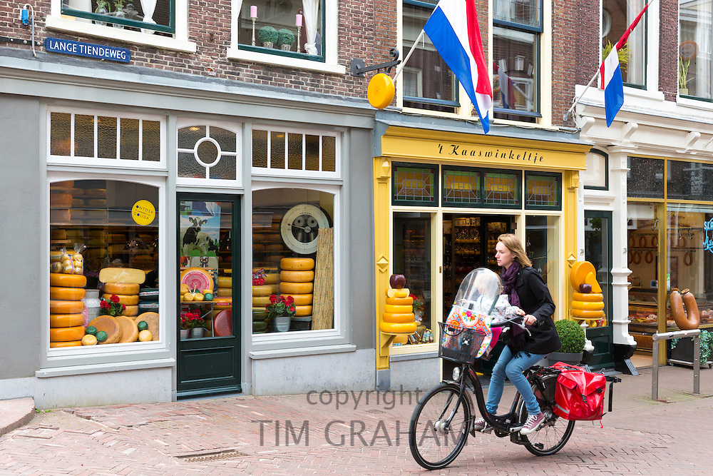 Woman with child cycles past cheese shop 't Kaaswinkeltje in Lange Tiendeweg, Gouda, Holland, The Netherlands