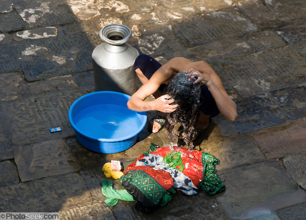 A person washes their hair at a public bath in Kathmandu, the largest city in Nepal (700,000 people).
