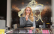 """Tennis great and Godiva Global Ambassador Caroline Wozniacki """"serves up"""" Soft Serve and introduces the limited edition """"Caroline"""" chocolate at Godiva in New York, Monday, Aug. 24, 2015, ahead of her appearance in the U.S. Open.  Godiva fans will receive a """"Caroline"""" chocolate with their purchase of a Soft Serve at participating New York City boutiques during the U.S. Open.  (Photo by Diane Bondareff/Invision for Godiva/AP Images)"""