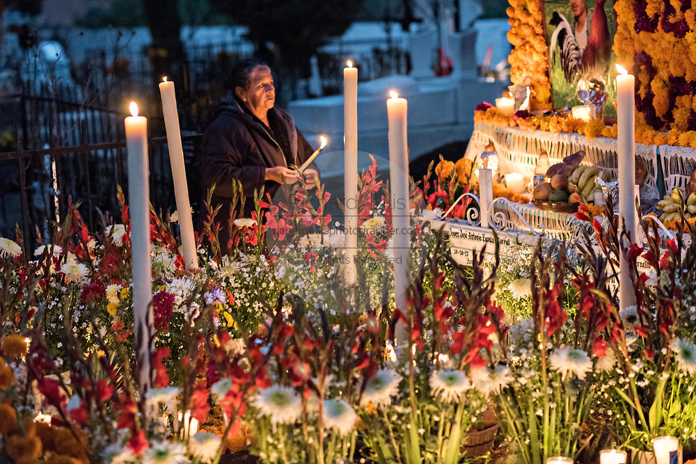 The mother of two brothers killed on the same day lights candles on their decorated gravesite during the Day of the Dead festival October 31, 2017 in Tzintzuntzan, Michoacan, Mexico.