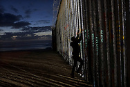 TIJUANA, MEXICO - JANUARY 06: A man prepares to climb on the U.S.-Mexico border wall on January 6, 2019 in Tijuana, Mexico. The U.S government is going into the third week of a partial shutdown with Republicans and Democrats at odds on agreeing with President Donald Trump's demands for more money to build a wall along the U.S.-Mexico border.(Photo by Sandy Huffaker/Getty Images)