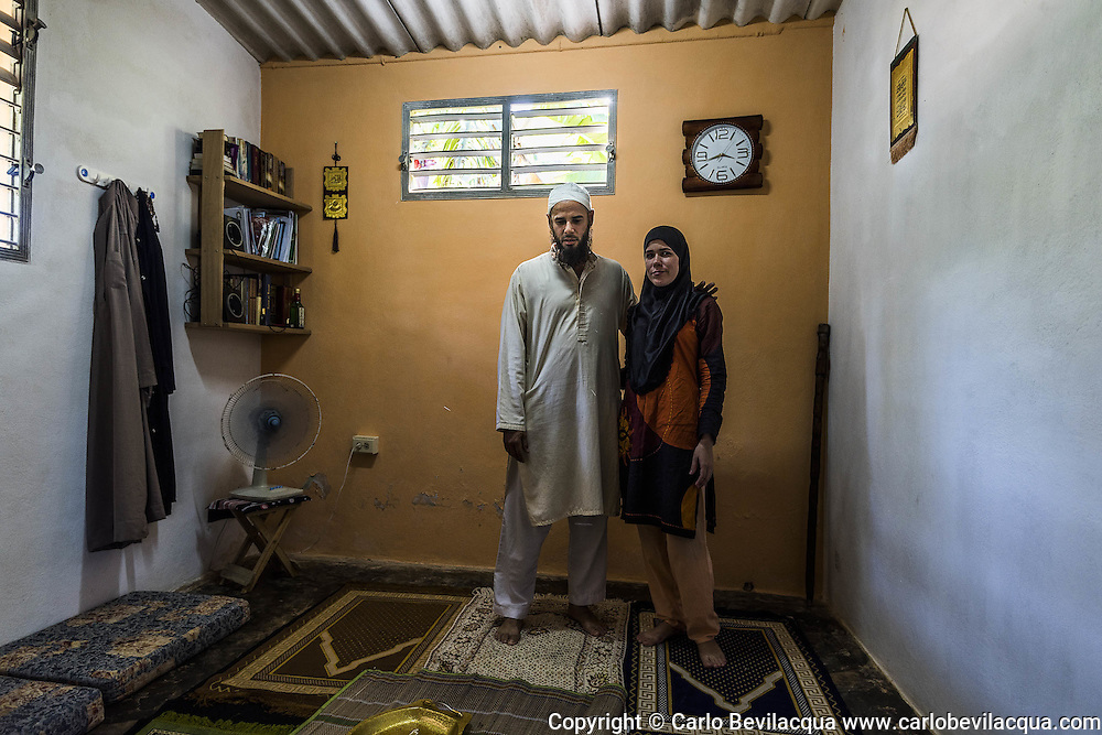 "Yusuf Ali and his wife Aisha in the ""musalla"" of their house near Varadero. Yusuf, once Joseph Alejandro, 37 yo from Varadero, converted to Islam while he was in Tenerife, when in a moment of depression nearly pushing him to suicide, he met a Belgian couple of Moroccan origins that introduced him to Islam. Aisha is 24 yo. She's a physiotherapist, works in a hospital and often suffers discrimination. Nevertheless, she's highly considered by her patients. She converted to Islam five years ago after meeting some Pakistani students at the university."