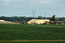 Mounds of sand and gravel line the perimeter of a gravel pit