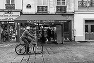 November 4, 2017 -- Rue St Antoine, Paris France --A cyclist rides past small shops in the Saint-Paul district in Paris. Editorial Use Only.