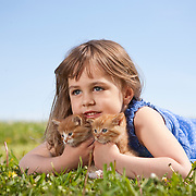 Smiling girl 4-6 years in dress lying on grass holding two kittens