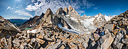 "Paso Quadrado affords a spectacular panorama south to Lago Quadrado, the North Fitz Roy Glacier, and peaks including Guillaumet, Mermoz, Fitz Roy, Cerro Torre, and Aguja Pollone (left to right), near El Chalten, Argentina, Patagonia, South America. We hiked scenic Rio Electrico Valley to Refugio Piedra del Fraile (""Stone of the Friar"", 14.5 km round trip) to stay overnight in dorms. A path from the refuge ascends very steeply to Paso Quadrado (gaining 1340 m vertically in 8.4 km round trip). The last kilometer climbs up steep snow which could require crampons if icy (but was passable in soft snow using our trailrunning shoes). Views keep improving as you ascend. Monte Fitz Roy is also known as Cerro Chaltén, Cerro Fitz Roy, or Mount Fitz Roy (3405 m or 11,171 ft elevation). The first Europeans recorded as seeing Mount Fitz Roy were the Spanish explorer Antonio de Viedma and his companions, who in 1783 reached the shores of Viedma Lake. In 1877, Argentine explorer Francisco Moreno saw the mountain and named it Fitz Roy in honour of Robert FitzRoy who, as captain of HMS Beagle, had travelled up the Santa Cruz River in 1834 and charted large parts of the Patagonian coast. Mt Fitz Roy was first climbed in 1952. Cerro is a Spanish word meaning hill, while Chaltén comes from a Tehuelche word meaning ""smoking mountain"", due to clouds that usually form around the peak. This image was stitched from multiple overlapping photos."