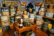 1800s bandboxes and hatboxes are arranged as in an old milliner's shop, at the Shelburne Museum near Lake Champlain, in Vermont, USA. Stackable bandboxes peaked in popularity between 1825-1850 as Americans moved cheaper and faster via canals and locomotives. Shelburne Museum is one of the finest, most diverse, unconventional museums of American folk art. Over 150,000 works are exhibited in 38 buildings, 25 of which are historic (relocated from New England and New York). Electra Havemeyer Webb, an avid collector of American folk art, founded the Museum in 1947.