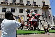Pessoas tiram fotos de um papai noel de 9 metros de altura que é instalado em frente a prefeitura de São Paulo durante a manhã deste sábado. Foto: Nelson Antoine/Frame