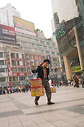 A porter carries shopping on poles across his shoulders, Chongqing, The People's Republic of China