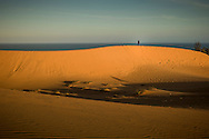 Distant figure stands on the massive sand dunes of Mui Ne, Binh Thuan Province, Vietnam, Southeast Asia