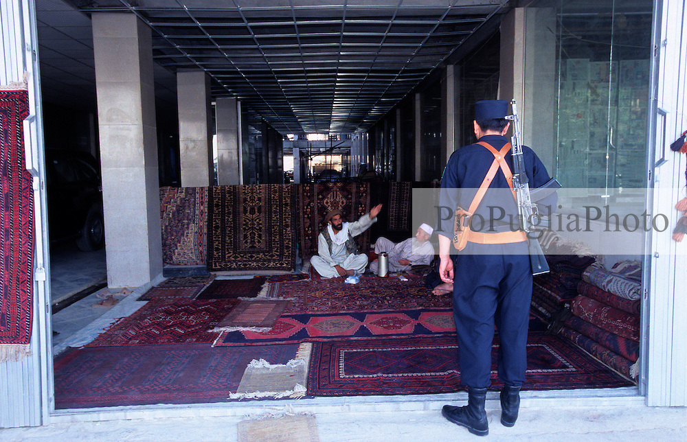 Kabul, 26 July 2005. A carpet seller has set up is temporary shop in a building under construction.