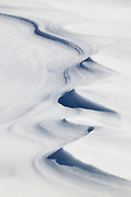 Strong winds shape a snowdrift at Paradise in Mount Rainier National Park, Washington. Relatively warm weather followed by freezing gives the snowdrift a hard crust.