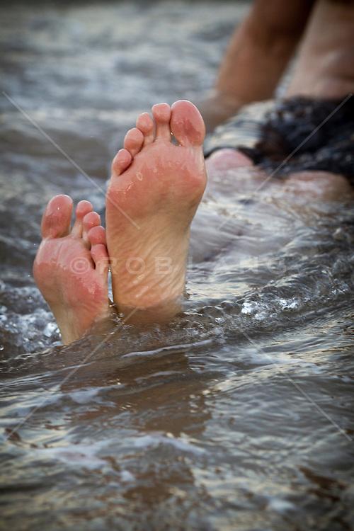 man's feet in the ocean