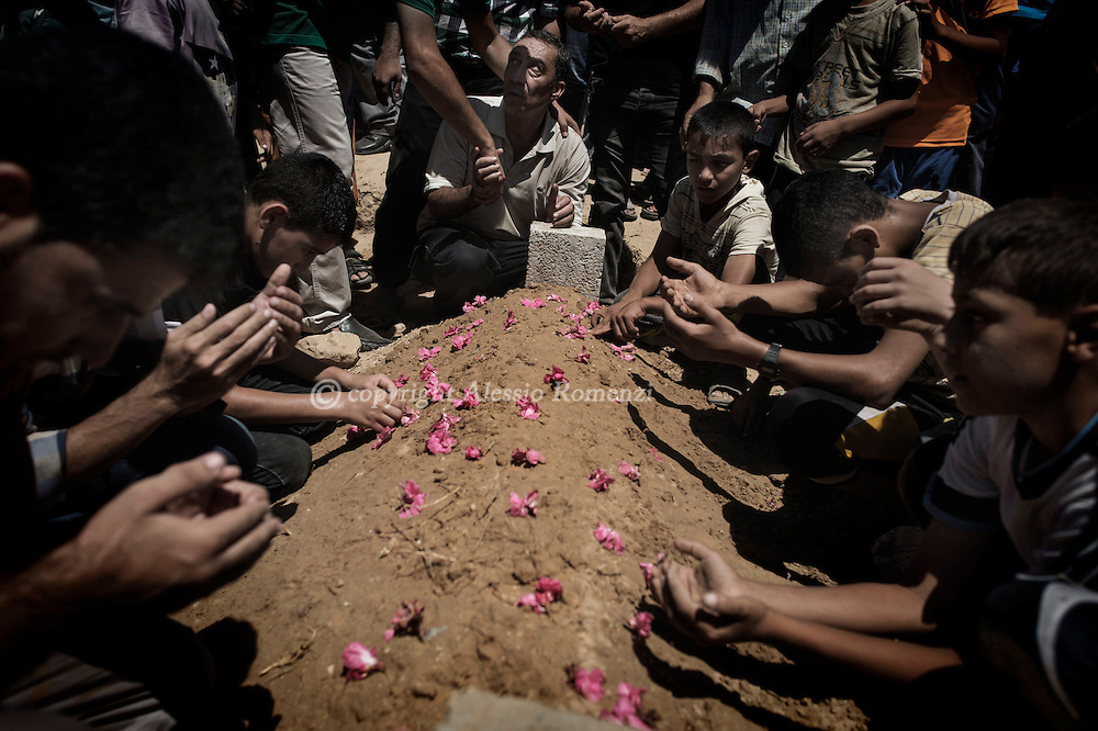 Gaza Strip, Deir Balah: Mourners pray on the grave of Mahmud Jaarouni 55 y.o. killed by an overnight Israeli airstrike in Deir Balah on August 10, 2012. ALESSIO ROMENZI