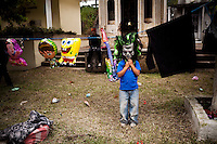 A boy hids in a mask that is for sale during Dia de los Muertos at Cementario General, in Guatemala City, Guatemala, on Tuesday, Nov. 1, 2011.