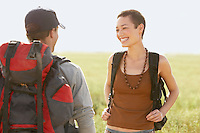 Two hikers talking standing in field