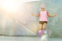 Young attractive woman exercising by jumping on rope