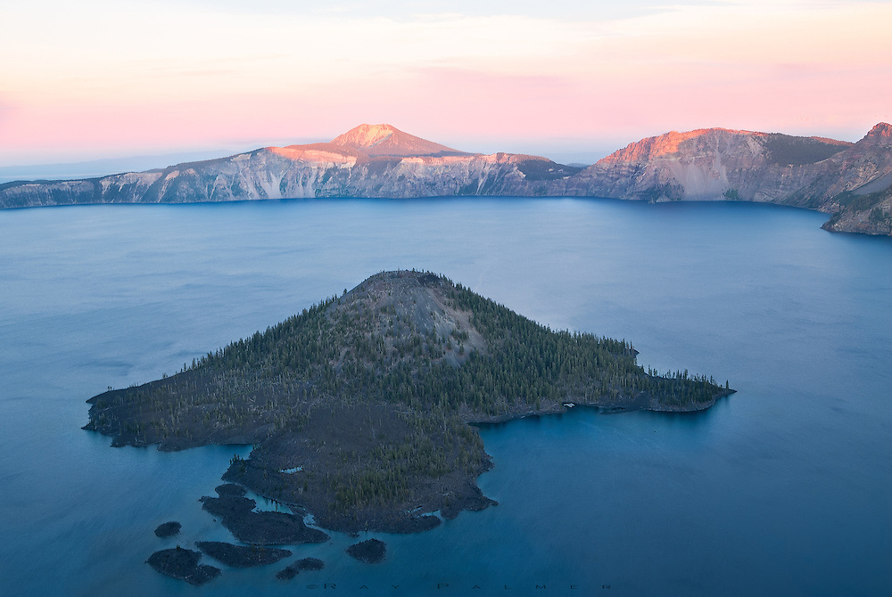 Wizard Island, Crater Lake, Oregon.  I saw you from far across the water, where shadows now walk up cliffsides, as if you were floating on a sea of blue.  I was taking the long way around to where you rose, so elegantly, from somewhere so deep.  From the moment I saw, I knew that was where I wanted to be.  I took my time along the rim, marvelling at water so blue, awed that what I was travelling around was a single mountain once,  how massive it must have been before it erupted, hundreds of centuries ago.  Reaching here, I sat high on the edge of the caldera, at a point so close.  And closeness showed the hardness of your beauty, the sharpness of your edges, the coldness of your landscape that the cloak of distance hid....the cinders of your self destruction.  In the end we probably all reveal what we are, but pretend we are not. And  I wondered if it was really worth knowing, as you floated on a sea of blue, under a sky of pink, just out of reach.
